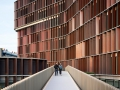 The copper-covered shutters of the façade function as movable climate shields, which, depending on weather conditions, automatically opens or closes, ensuring a comfortable indoor climate.
