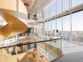 A continuous sculptural spiral staircase visually and physically connects the open fifteen floor atrium, creating an extensive three-dimensional sense of space.