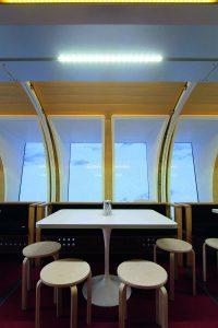 Aufenthaltsraum mit Tischen und Stühlen.