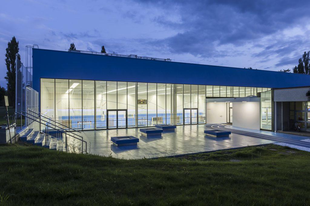 Blaue Sporthalle bei Nacht.