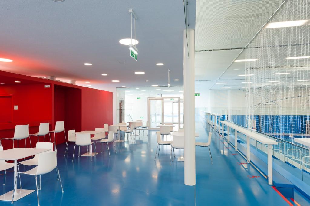 Blau und roter Aufenthaltsraum mit Sesseln und Stühlen.