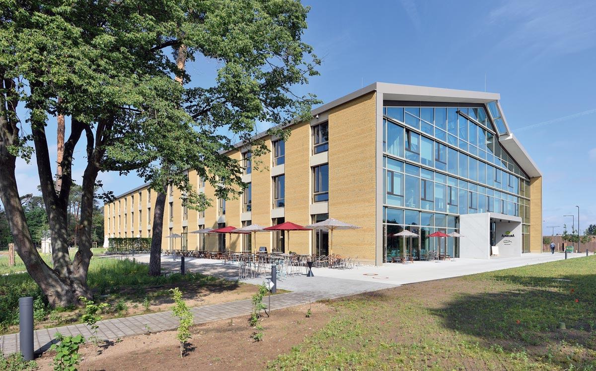 Der Alnatura Campus in Darmstadt wurde von haascookzemmrich STUDIO 2050 als Firmensitz für die gleichnamige Marke gestaltet. Durch die Expertise von Martin Rauch konnte hier mit industrieller Vorfertigung Europas größtes Gebäude mit Lehmfassade geschaffen werden.
